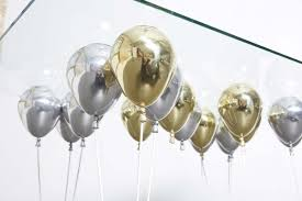 silver balloons suspended by shiny gold and silver balloons up dining table