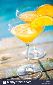 champagne glasses with orange slice mimosa cocktail summer pool