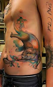 otter chasing a fish watercolor side piece best tattoo design ideas