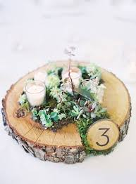 wood centerpieces picture of a wood slice with moss and succulents candles and a