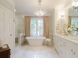 transitional bathroom features a crystal chandelier over a