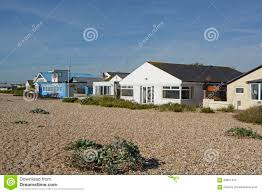 bungalows on beach at pagham west sussex england editorial stock