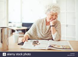 elegant grandmother sitting at home reading a magazine stock photo