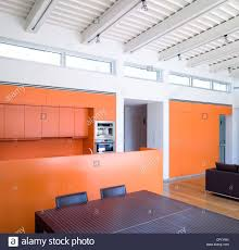 open plan kitchen dining living room with orange walls and line