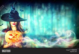 halloween witch with a magic pumpkin in a dark forest beautiful