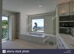 Spanish Bathroom Design by Window Above Bath In White Spanish Bathroom With White Shutters On