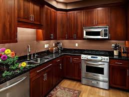 Titusville Cabinets Cherry Wood Kitchen Cabinets With Silver Appliances And Black