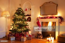 christmas tree and gifts near fireplace in living room stock photo
