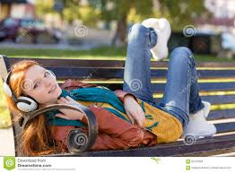 joyful smiling relaxing on bench in park using headphones