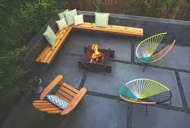modern backyard with wooden bench and metal outdoor fire pit