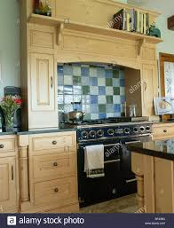 blue green and cream ceramic tiles above black range oven in