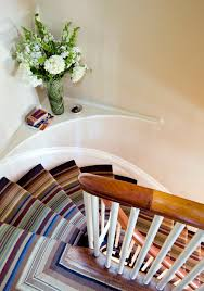 decorating banister with curved stair and custom rug also floral