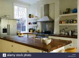 iroko wood worktop on island in kitchen with open shelving stock