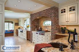 a brick arch over a range top is the centerpiece of this kitchen