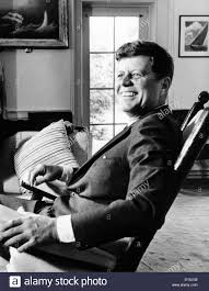 a relaxed president kennedy sits in his rocking chair in the oval