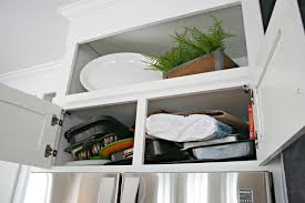 how to easily organize awkward pans above the fridge from thrifty