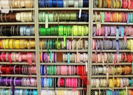 ribbon shop haberdashery shelves of coloured ribbon reels and trims in fabric