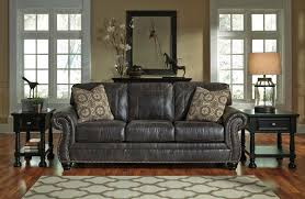 faux leather sofa with rolled arms and nailhead trim by benchcraft