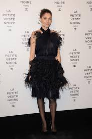 laetitia casta wears lots of feathers in a black dress fashion blog