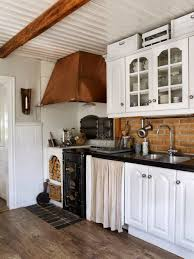 traditional kitchen with white cabinets and copper hood installed