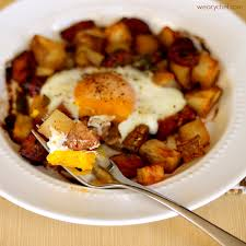 dinner egg recipes baked egg over roasted potatoes and sausage the weary chef