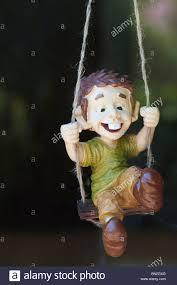 swinging boy ornament hanging in a shop window uk stock