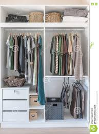 clothes and dress hanging on rail in white closet stock photo