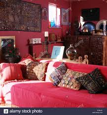 embroidered indian cushions on sofa with red throw in red stock