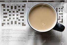 top of coffee cup a full cup of tea sitting on top of a semi solved crossword puzzle