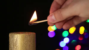 Hand Lighting Christmas Candle With A Match And With Abstract Lights
