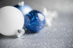 blue and white ornaments on glitter background merry