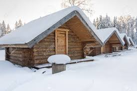small snowy cosy log cabins in row at very snowy winter day stock