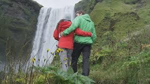 iceland tourists people walking by waterfall skogafoss romantic
