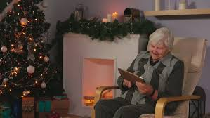 what to get an elderly woman for christmas elderly woman reads the message on a plate next to christmas tree