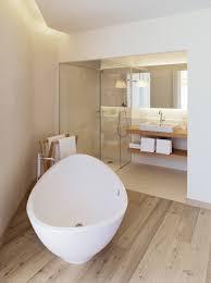 oval acryli tub on unpolished hardwood floor combined with