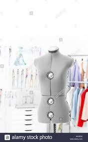 gray tailoring mannequin on a background of hanging clothes