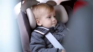 little boy is sitting in the car seat and looking with interest