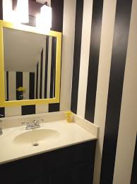 black vanity with lights black stripes wall paint in small bathroom with yellow frame of