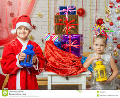two girls in christmas costumes are with candlesticks from the bag