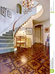 luxury foyer with designed hardwood floor and spiral staircase