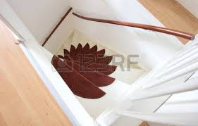 white wooden stairs with mats going upstairs stock photo
