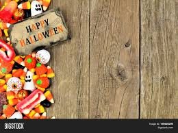 kids halloween candy background happy halloween tag with candy side border against a rustic wood