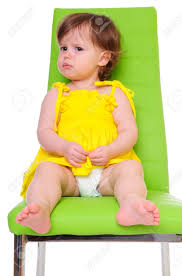 little in a yellow dress sits on a green chair child focused