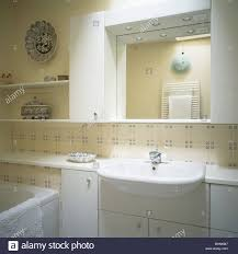 mirror above basin in fitted vanity unit in modern bathroom with