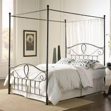 bedroom brown wooden canopy beds with white fabric curtains and
