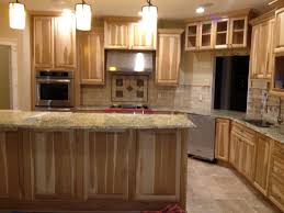kitchen with hickory cabinets and travertine backsplash with