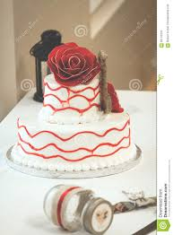 simple red and white wedding cake with rose on top stock photo