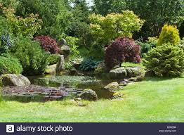 grit stone rocks bushes trees and pond in garden design by bahaa