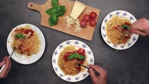 cutting board plates serving and spaghetti with friends top view on dinning