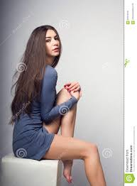 young lady in a short dress with bare legs playfully sitting on a